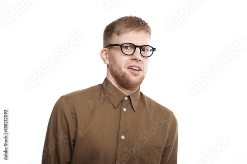 Fotografie, Tablou  Horizontal shot of young bearded male of European appearance wearing eyeglasses and shirt having disgusted displeased expression, staring at camera with disgust