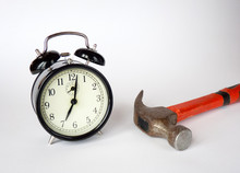 Alarm Clock And Hammer Are On The Table. White Background. The Beginning Of The Morning.