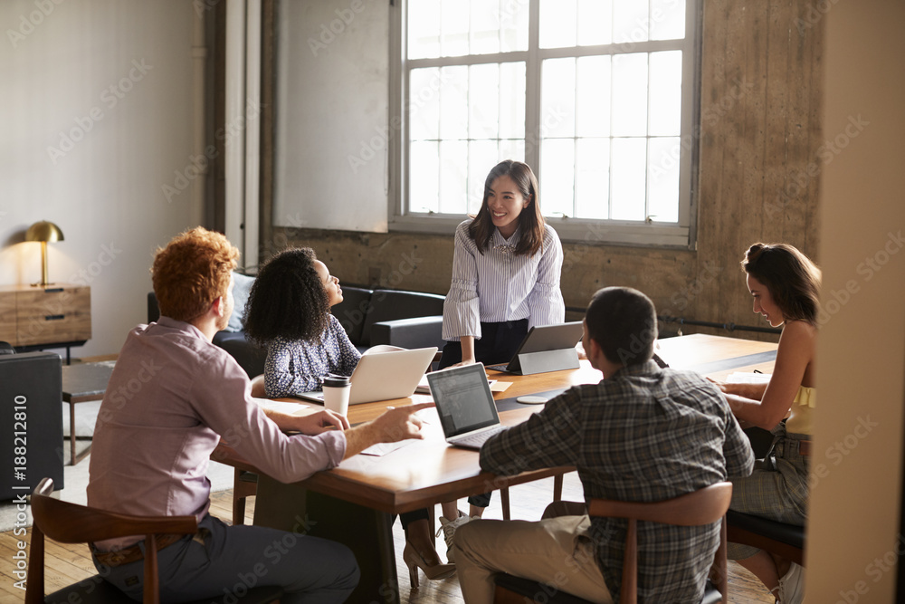 Fototapeta Smiling woman standing to address colleagues at a work meeting