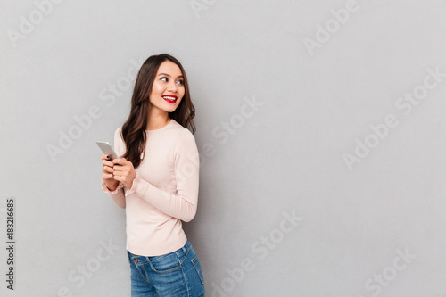 Photographie  Satisfied smiling adult girl with red lips holding mobile phone turning back ove