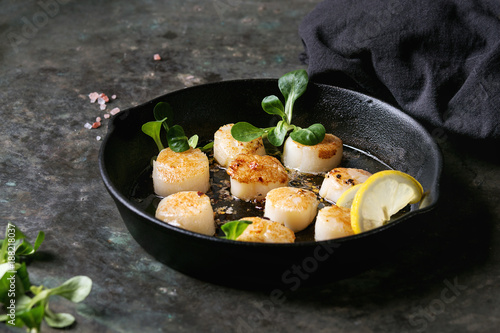 Fried scallops with butter lemon spicy sauce in cast-iron pan served with green salad and textile napkin over old dark metal background Fototapet