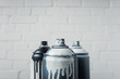 canvas print picture close up view of spray paint in cans with brick wall background