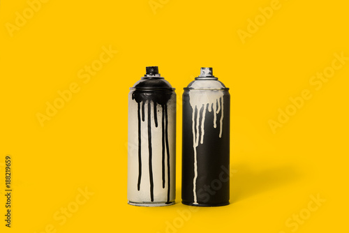 close up view of black and white aerosol paint in cans isolated on yellow - 188219659
