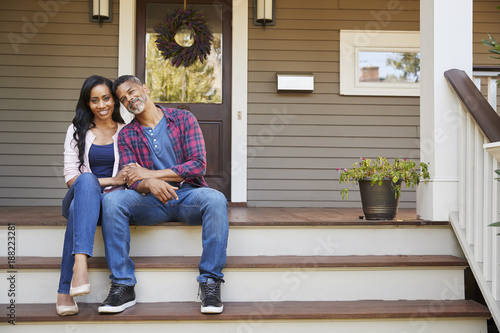 Photographie  Couple Sitting On Steps Leading Up To Porch Of Home