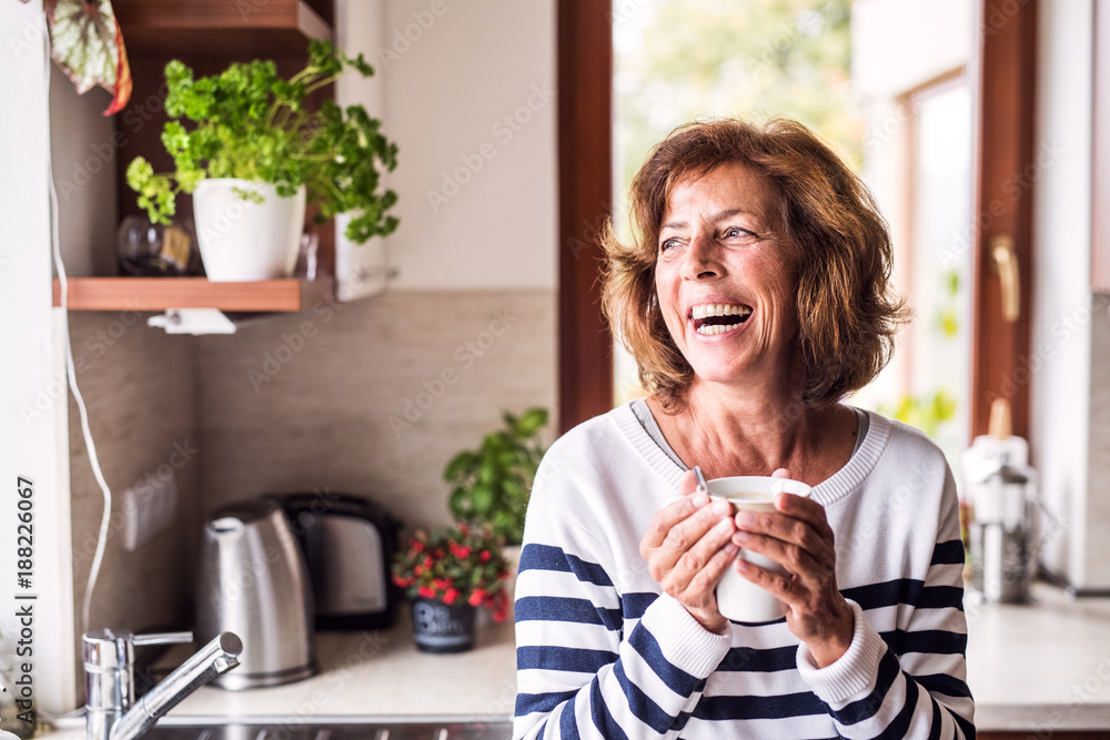 Fototapety, obrazy: Senior woman holding a cup of coffee in the kitchen.