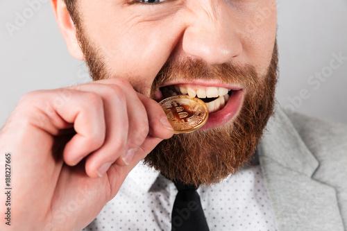 Fotografía  Close up portrait of a man biting golden bitcoin