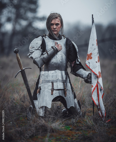 Girl in image of Jeanne d'Arc in armor kneels with flag in her hands and sword on meadow Tableau sur Toile