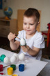 Having fun on Easter egg hunt. Children with colorful eggs in basket. Toddler kid boy play indoor, selective focus