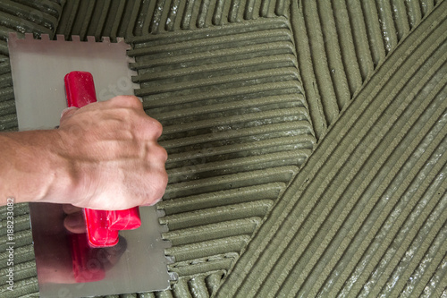 Worker hand with trowel tool for tiles installation making mortar adhesive on fl Wallpaper Mural