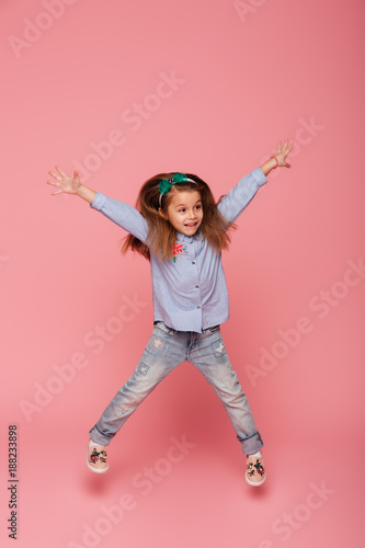 Full-length picture of joyful carefree child jumping and throwing hands up in the air being isolated over pink background