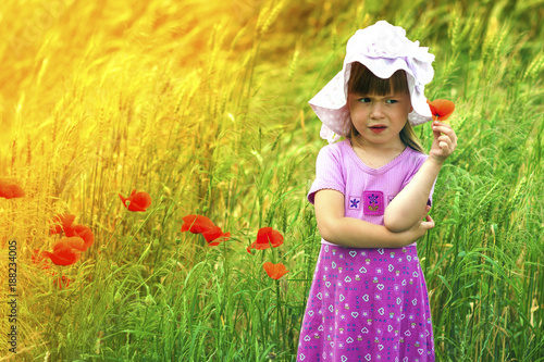 Valokuva  Little  displeased and dissatisfied cute girl with red flower