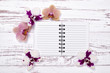 notepad on old wooden table decorated with flowers