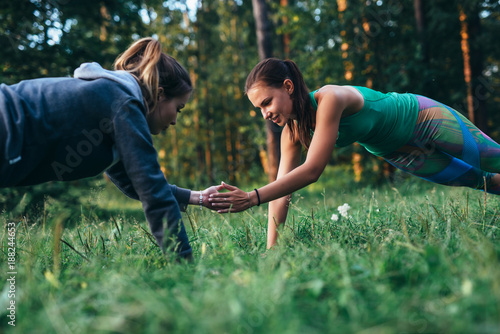 Fotografía  Two girls doing buddy workout outdoors performing push-ups to clap on grass