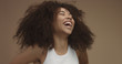 canvas print picture - mixed race black woman portrait with big afro hair, curly hair in beige background. Natural laughing