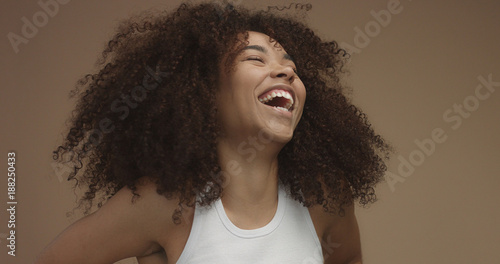mixed race black woman portrait with big afro hair, curly hair in beige background. Natural laughing