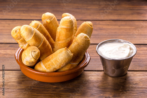 Tequeños, Typical Venezuelan snack with garlic sauce on a wood background