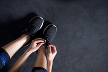 Woman Tying Running Shoes On Black Floor Background In Gym.