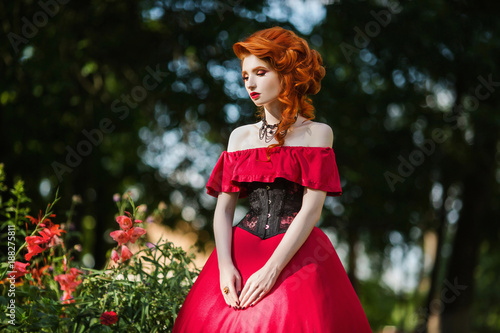3136db9292ed Beautiful red-haired girl in a red dress and in black corset on a green
