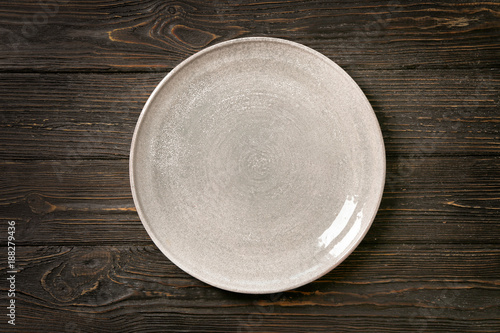 Ceramic plate on wooden background Fototapeta
