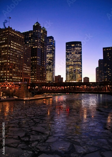 Foto op Plexiglas Chicago City night lights illuminate and reflect off of a frozen Chicago River on a January evening in winter.