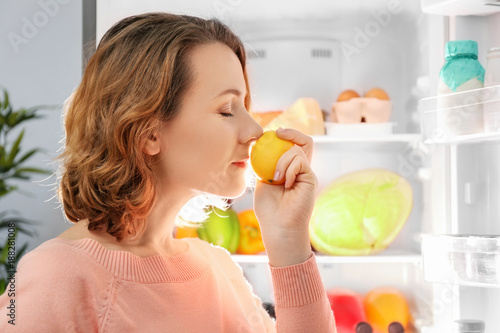 Fototapeta Beautiful woman with fresh lemon standing near refrigerator obraz