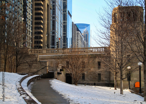 Foto op Plexiglas Chicago Path along Chicago riverwalk during winter midday with snow piles.