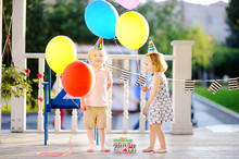 Little Boy And Girl Having Fun And Celebrate Birthday Party With Colorful Balloons