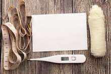 White Sticky Note With Empty Space For A Text On Wooden Background. Health Concept With Thermometer Bandage And Metre