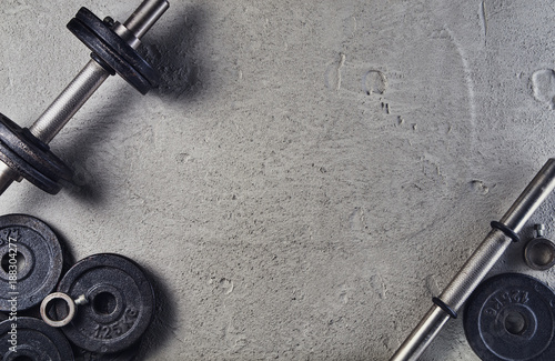 Spoed Foto op Canvas Fitness Fitness or bodybuilding concept background. Product photograph of old iron dumbbells on grey, conrete floor in the gym. Photograph taken from above, top view with lots of copy space