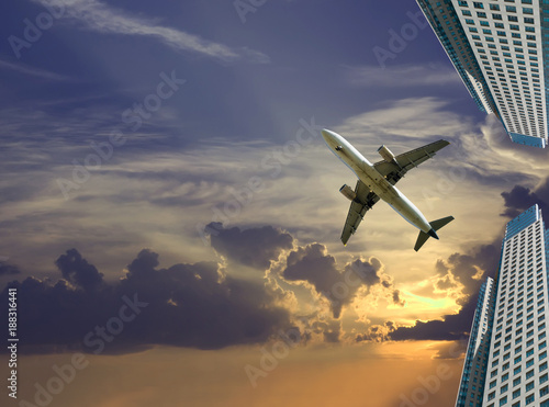 airliner in sky on skyscrapers background Canvas Print
