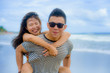 beautiful Asian Chinese couple with boyfriend carrying woman on her back and shoulders at the beach smiling happy in love enjoying holidays