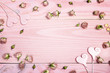 Decorative hearts with dried rose flowers on pink wooden background with copy space. Flowers composition.