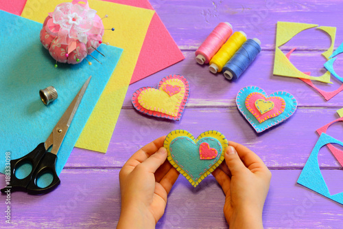 Child holds a felt heart gift in his hands. Child show a felt heart gift. Heart ornaments, scissors, felt sheets on a wooden table. Homemade Valentines Day decor crafts. Hand sewing projects for kids