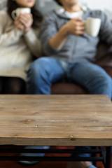 テレビを見ながらコーヒーを飲む若い夫婦
