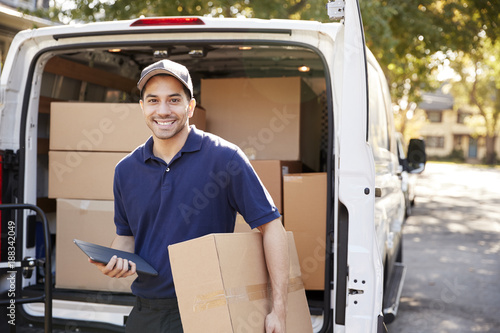 Fotografía  Portrait Of Courier With Digital Tablet Delivering Package
