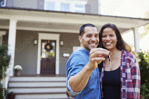 Valokuva  Portrait Of Couple Holding Keys To New Home On Moving In Day