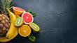 Leinwandbild Motiv Fresh Tropical Fruits. Pineapple, coconut, kiwi, orange, pomegranate, grapefruit. On a wooden background. Top view. Free space for text.