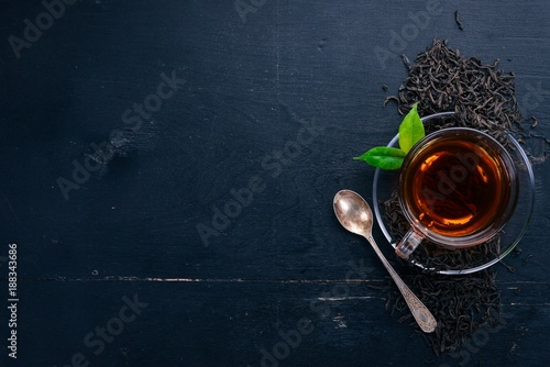 A cup of black tea on a wooden background. Top view. Copy space.