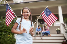 Portrait Of Girl Outside Family Home Holding American Flags