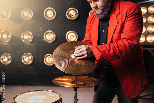 In de dag Muziekband Bearded drummer in red suit on the stage