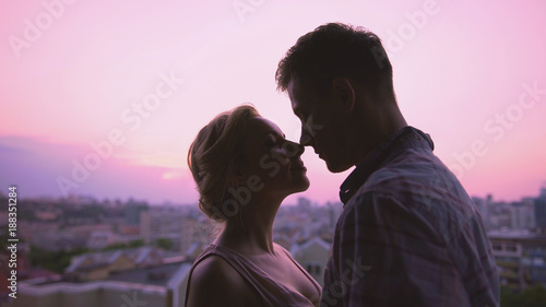 Vászonkép Cute lovers gently hugging, standing on roof, beautiful sunset city background