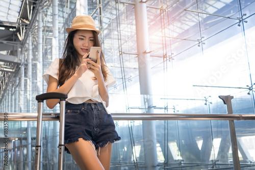 Plakat Azjatycki kobieta nastolatek używa smartphone przy lotniskowym terminal z bagaż walizką i plecakiem dla podróży w urlopowym lata relaksującym czekanie lota transporcie online sprawdza wewnątrz lub rezerwuje bilet