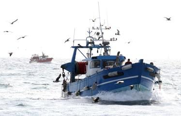 chalutiers en mer pris à contre-jour