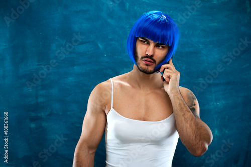 Transsexual male person wearing blue wig and female cloth talking on the  phone e5a0be76c