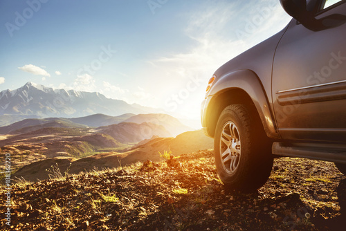 Keuken foto achterwand Bruin Big 4x4 car against sunset and mountains