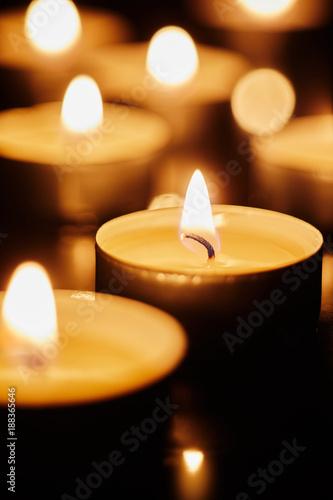 Fotografía  Burning tea light candles in darkness