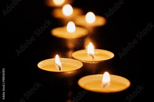 Fotomural  Burning votive candles on dark background