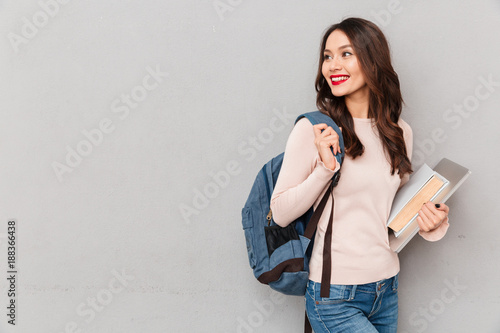 Obraz Image of smart woman with backpack studying in college holding book and laptop over gray wall - fototapety do salonu