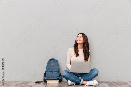 Photo  Horizontal image of female looking upward while reading or communicating online
