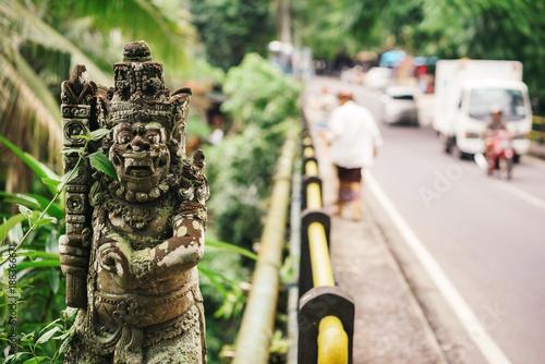 Statues of a Hindu god or demons on a transport bridge with cars and tourists, Bali, Indonesia Billede på lærred